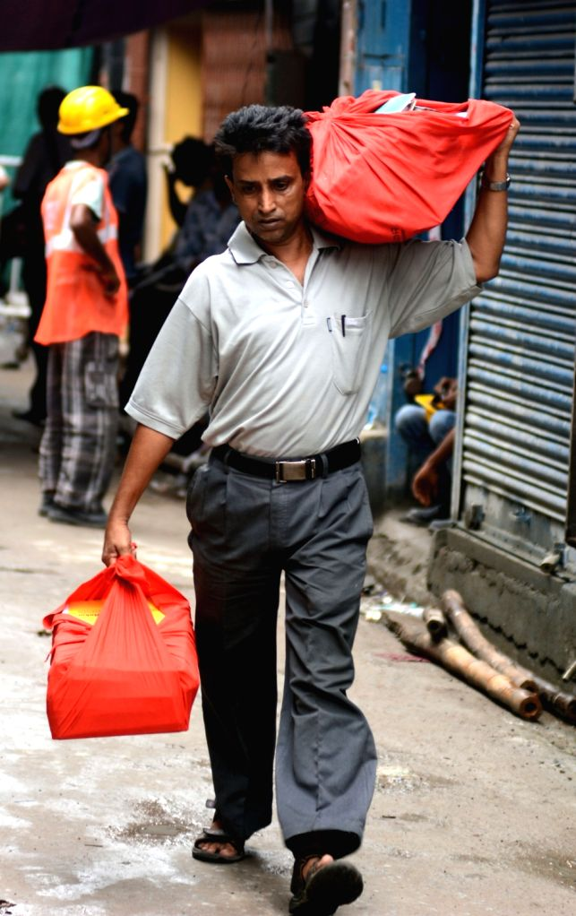 Residents carry their belongings as they evacuate Bowbazar area, where several houses have been damaged owing to tunnel boring for East-West Metro corridor in Kolkata on Sep 12, 2019.