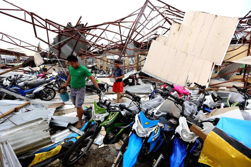 Residents clear the debris brought by the strong wind and heavy rain from Typhoon Haima in Cagayan Province, the Philippines, Oct. 20, 2016. At least eight ...