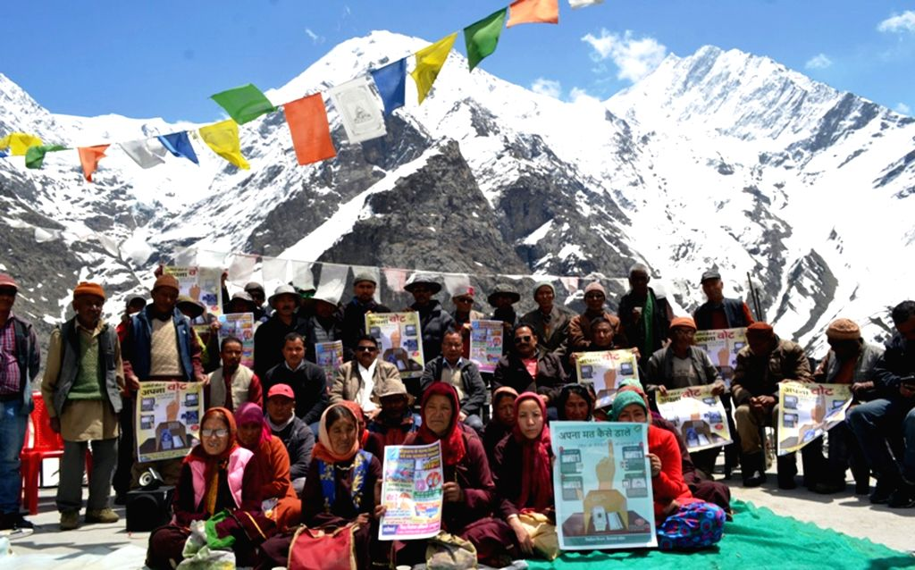 Residents hold placards as they participate in a voters' awareness campaign, encouraging people to vote in the forthcoming Lok Sabha elections, in Lahaul, Himachal Pradesh on May 4, 2019.