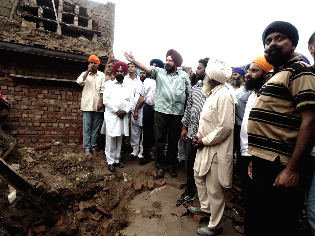 Residents remove debris after roof of a house collapsed due to heavy rainfall at a village in Gurdaspuir on Sept. 6, 2014.