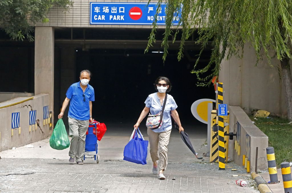 Residents rush to leave home after getting an evacuation order near the core area of explosion site in Tianjin, north China, Aug. 15, 2015. All people within 3-km ...