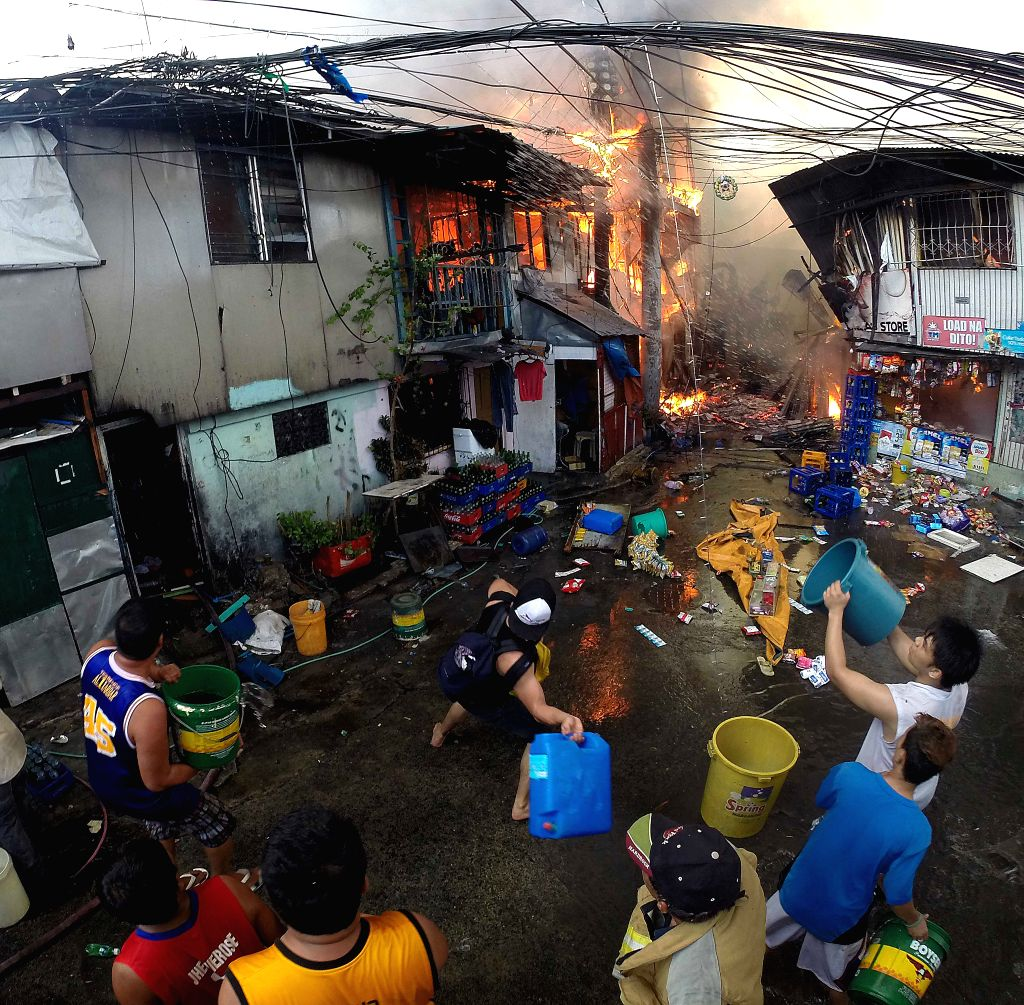 Residents throw buckets of water as they try to put out a fire at a slum area in Manila, the Philippines, Dec. 4, 2015. More than 500 shanties were razed in the fire, ...