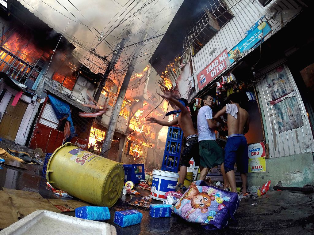 Residents try to salvage items from a fire scene at a slum area in Manila, the Philippines, Dec. 4, 2015. More than 500 shanties were razed in the fire, leaving 1,000 ...