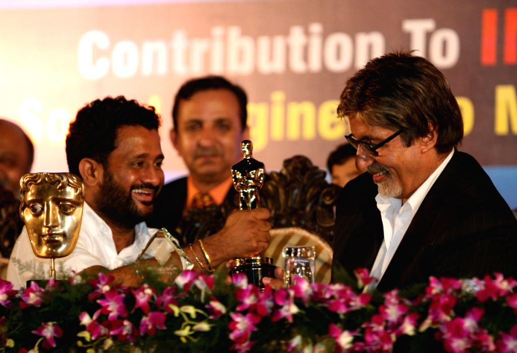 Resul Pukootty is ecstatic as he shows off his Oscar trophy to Amitabh Bachchan at an award ceremony.