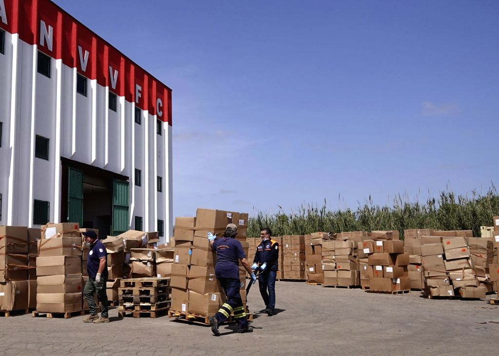 Retired firefighters transfer boxes of medical supplies outside a warehouse near Fiumicino airport in Rome