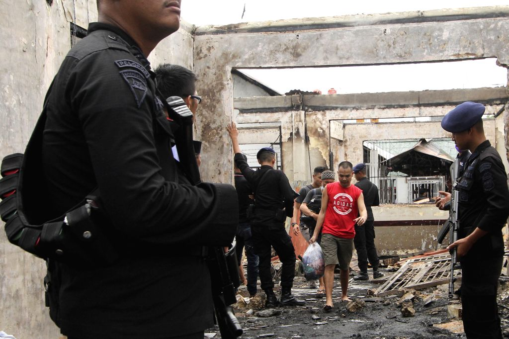 RIAU, May 11, 2019 - Indonesian police officers stand guard at the site of a fire at a prison in Siak Sri Indrapura in Riau province, Indonesia, May 11, 2019. Rioting and fire broke out at the prison ...