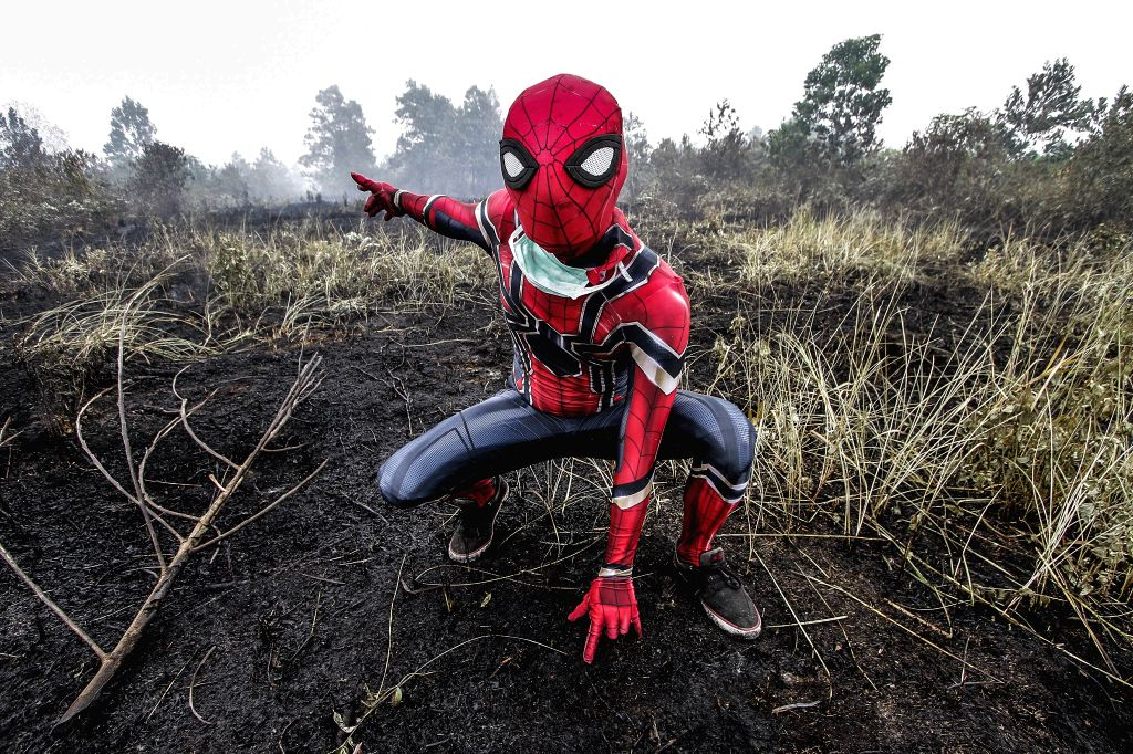 RIAU, Sept. 13, 2019 - A man wearing Spiderman's costume poses on peatland fire at Kampar, Riau, Indonesia, Sept. 12, 2019.