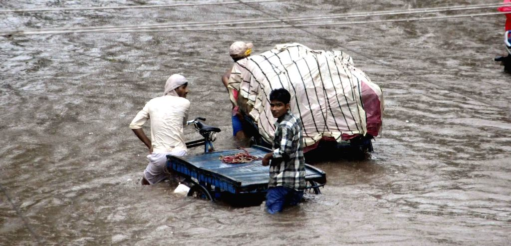 Rickshaw pullers struggle through waterlogged streets of Patna on Aug 14, 2014.