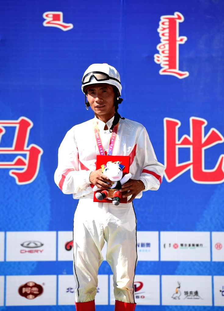 Rider Dong Chunhong from north China's Inner Mongolia Autonomous Region attends the awarding ceremony for the 8,000 meters horse racing event of the 10th National ...