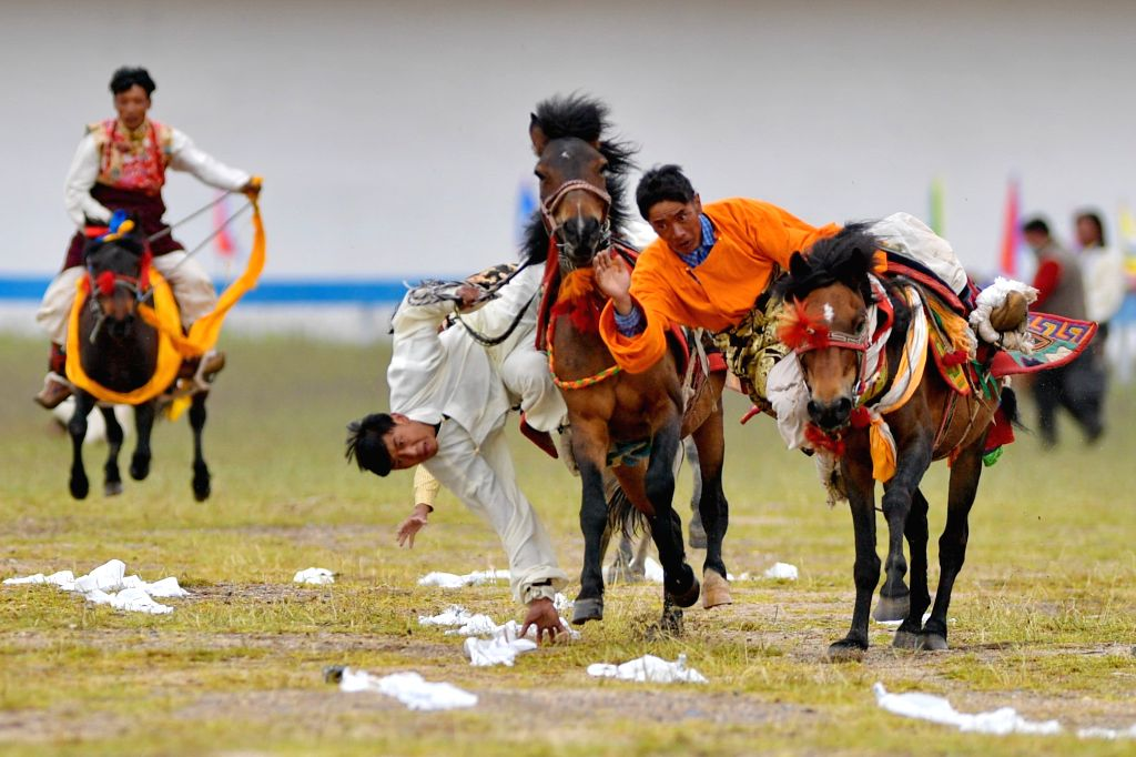 Riders compete during a horse racing event in Nagqu of southwest China's Tibet Autonomous Region, Aug. 11, 2020.