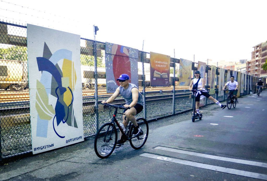 Riders pass by murals during the Murals of Gratitude Exhibition at Gastown in Vancouver, British Columbia, Canada, July 5, 2020. The exhibition showcased 35 murals ...