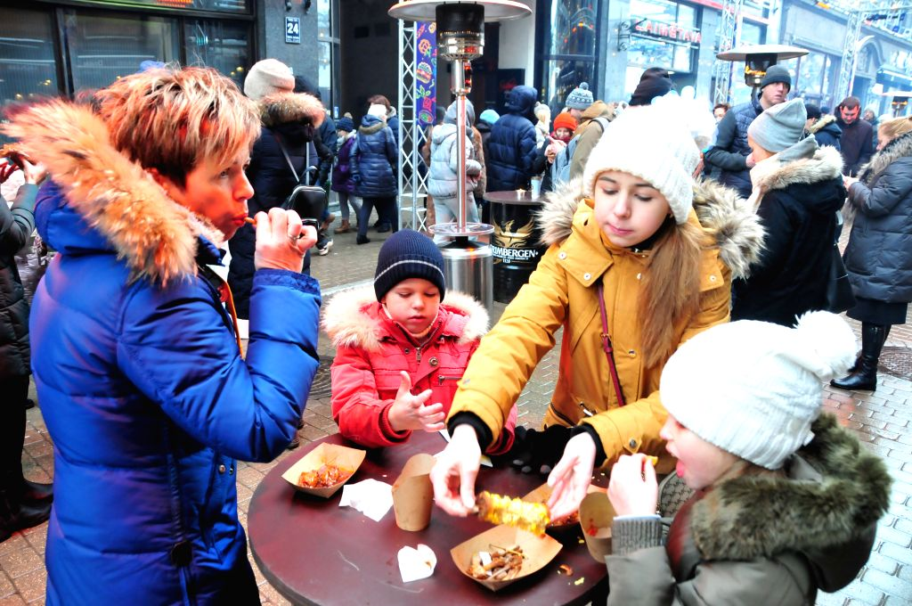 RIGA, Jan. 13, 2019 (Xinhua) -- Visitors enjoy food during Riga Street Food Festival in the Old Town of Riga, capital of Latvia, Jan. 12, 2019. Best available winter season specialities were offered by some chefs of well-known local restaurants durin