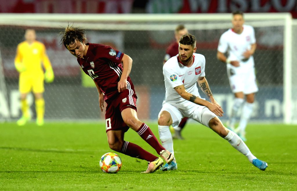 RIGA, Oct. 11, 2019 - Latvia's Janis Ikaunieks (L) vies with Poland's Mateusz Klich during the UEFA Euro 2020 qualifying round Group G match between Latvia and Poland in Riga, Latvia, Oct. 10, 2019.