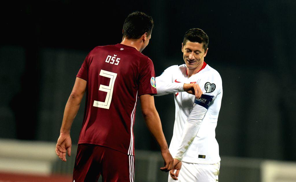 RIGA, Oct. 11, 2019 - Poland's Robert Lewandowski (R) talks to Latvia's Marcis Oss during the UEFA Euro 2020 qualifying round Group G match between Latvia and Poland in Riga, Latvia, Oct. 10, 2019.