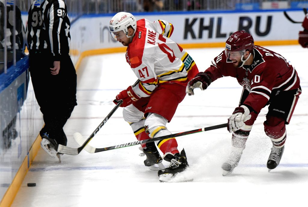 RIGA, Oct. 30, 2019 - Lauris Darzins (R) of Riga Dinamo vies with Kory Cane of Kunlun Red Star during the 2019-2020 Kontinental Hockey League (KHL) ice hockey tournament in Riga, Latvia, Oct. 29, ...