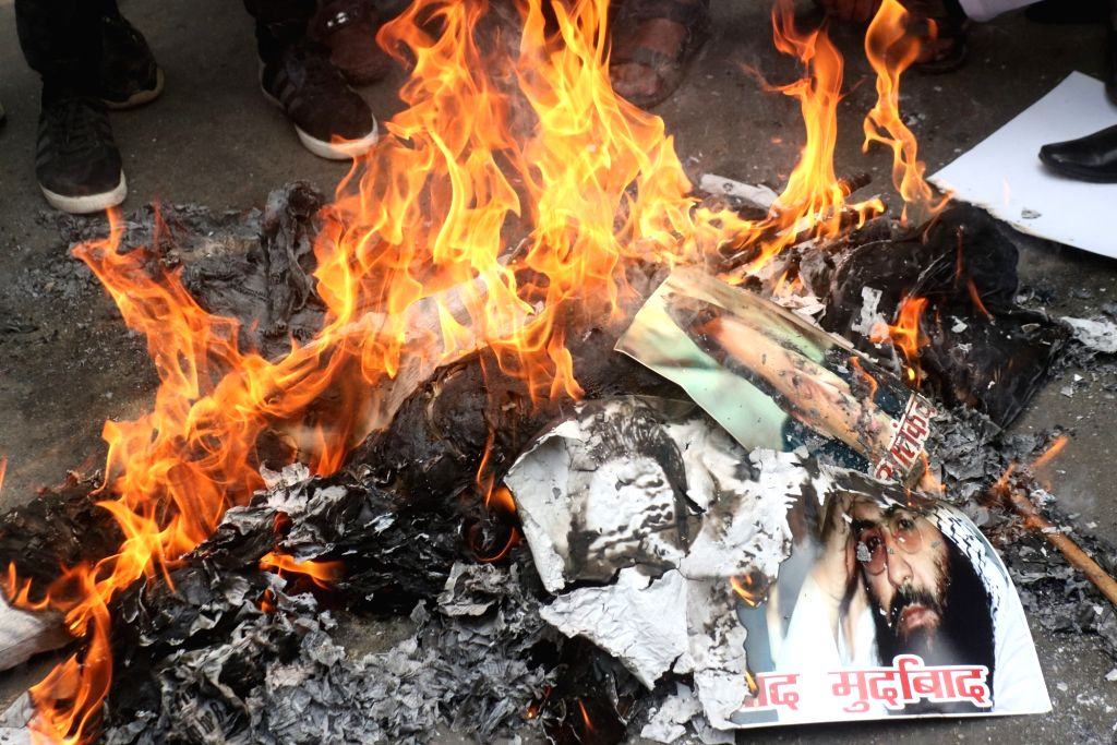Right wing activists burn pictures of Pakistan Prime Minister Imran Khan and Jaish chief Maulana Masood Azhar during a protest against suicide attack on a CRPF bus in Jammu and Kashmir's ... - Imran Khan