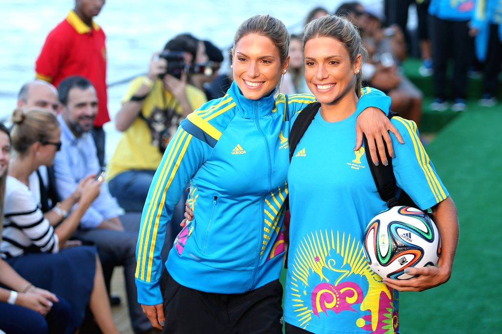 Brazilian synchronised swimming twins Bia and Branca Feres present the uniforms designed for FIFA World Cup volunteers on a fashion show during Fashion Rio .