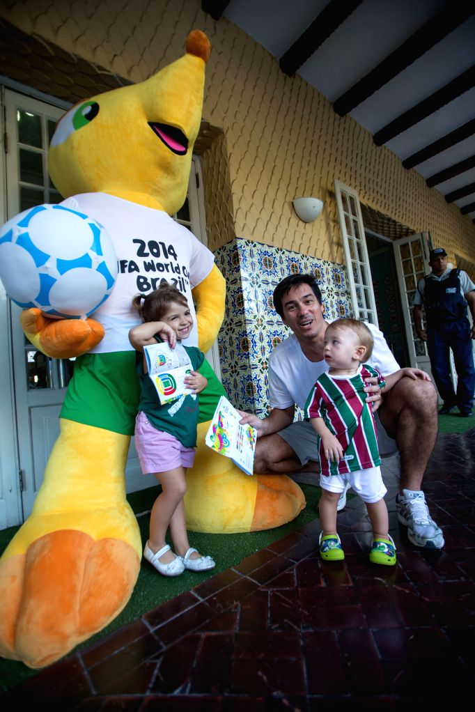 """A man and his children pose with the FIFA World Cup mascot """"Fuleco"""" outside a ticketing center located at the Botafogo football club in Rio de ..."""