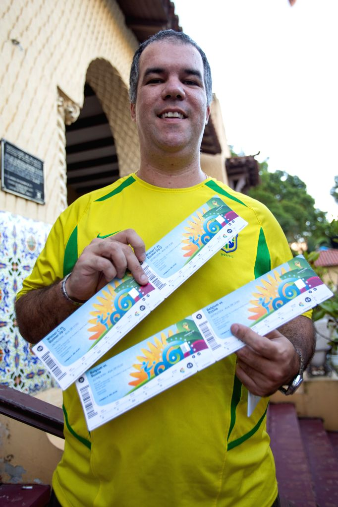 Rafael Elvans poses with his tickets outside a ticketing center located at the Botafogo football club in Rio de Janeiro, Brazil, April 18, 2014. Ticketing ..