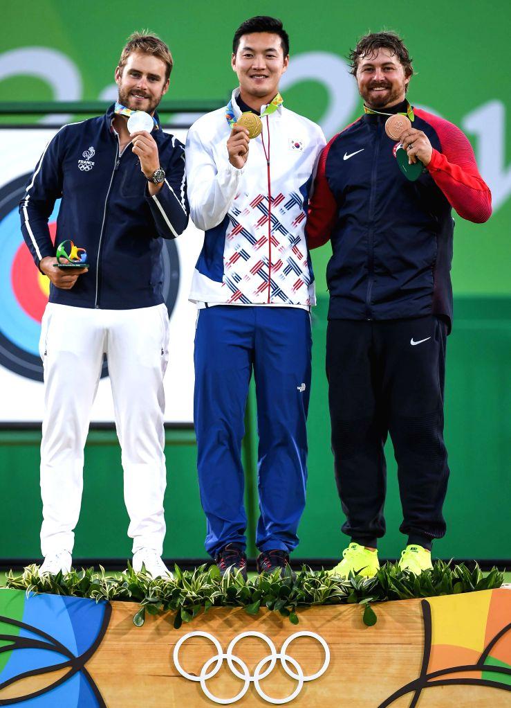 RIO DE JANEIRO, Aug. 12, 2016 - Gold medalist South Korea's Ku Bonchan (C) , silver medalist France's Jean-Charles Valladont (L), bronze medalist Brady Ellison of the United States of America show ...