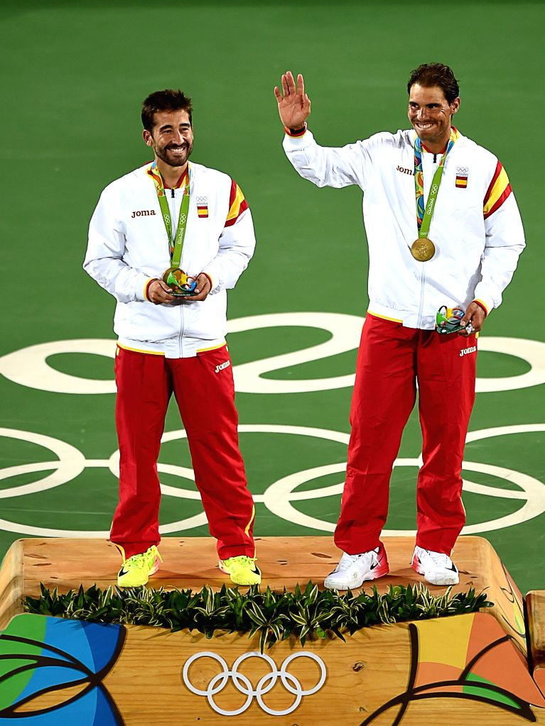 RIO DE JANEIRO, Aug. 12, 2016 - Rafael Nadal (R) and Marc Lopez of Spain celebrate at the awarding ceremony of men's doubles tennis at the 2016 Rio Olympic Games in Rio de Janeiro, Brazil, on Aug. ...