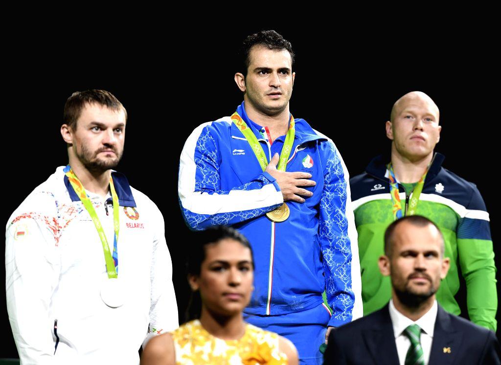 RIO DE JANEIRO, Aug. 13, 2016 - Gold medalist Iran's Sohrab Moradi (C behind), silver medalist Belarus's Vadzim Straltsou (L behind), bronze medalist Lithuania's Aurimas Didzbalis (R behind) attend ...