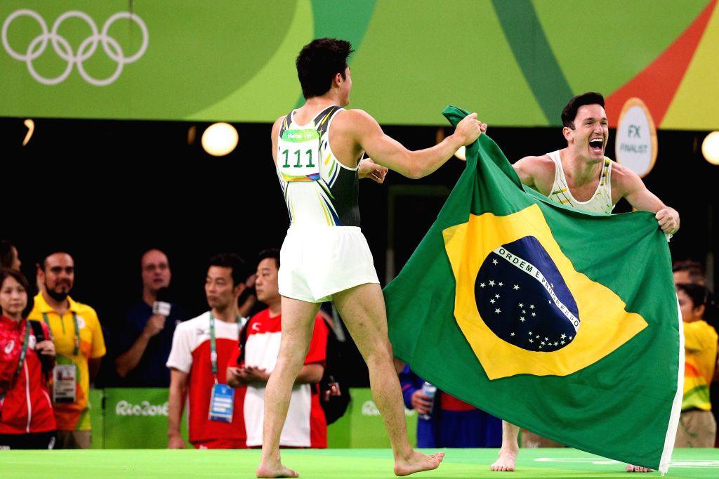 RIO DE JANEIRO, Aug. 14, 2016 - Diego Hypolito (R) and Arthur Mariano of Brazil celebrate after the men's floor exercise final of Artistic Gymnastics at the 2016 Rio Olympic Games in Rio de Janeiro, ...