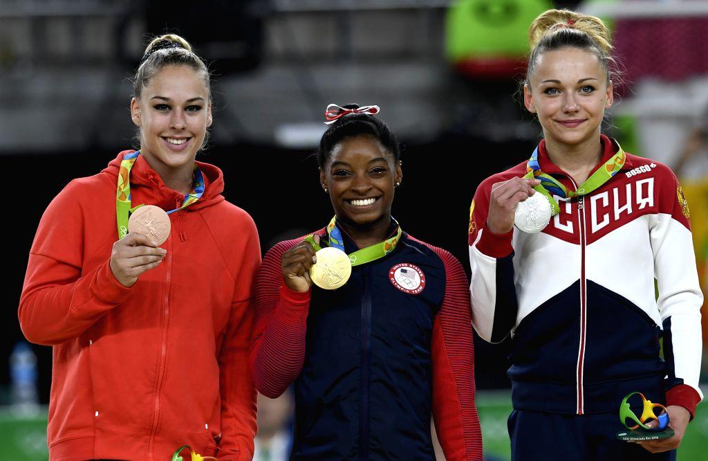 RIO DE JANEIRO, Aug. 14, 2016 - Gold medalist Simone Biles (C) of the United States of America, silver medalist Russia's Maria Paseka (R), bronze medalist Switzerland's Giulia Steingruber attend the ...
