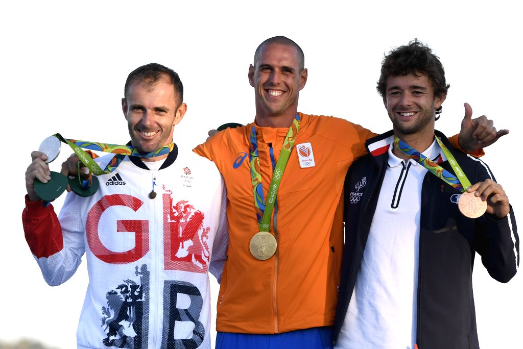 RIO DE JANEIRO, Aug. 14, 2016 - Gold medalist the Netherlands' Dorian van Rijsselberghe (C), silver medalist Britain's Nick Dempsey (L) and bronze medalist France's Pierre Le Coq attend the awarding ...