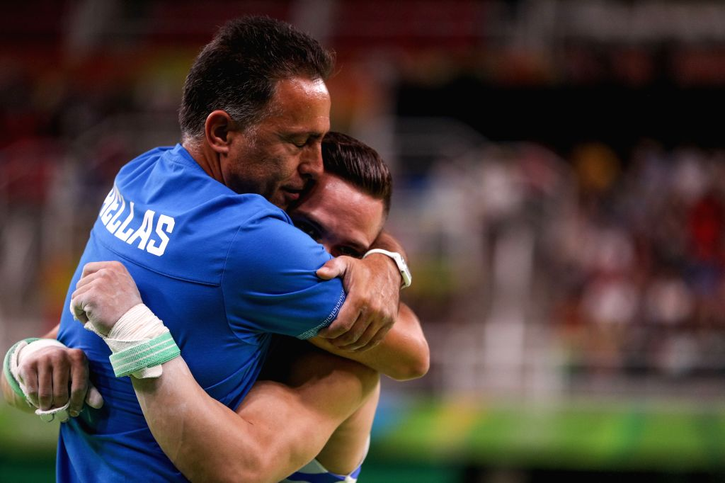 RIO DE JANEIRO, Aug. 15, 2016 - Greece's Eleftherios Petrounias (R) hugs with his coach during the men's rings final of Artistic Gymnastics at the 2016 Rio Olympic Games in Rio de Janeiro, Brazil, on ...