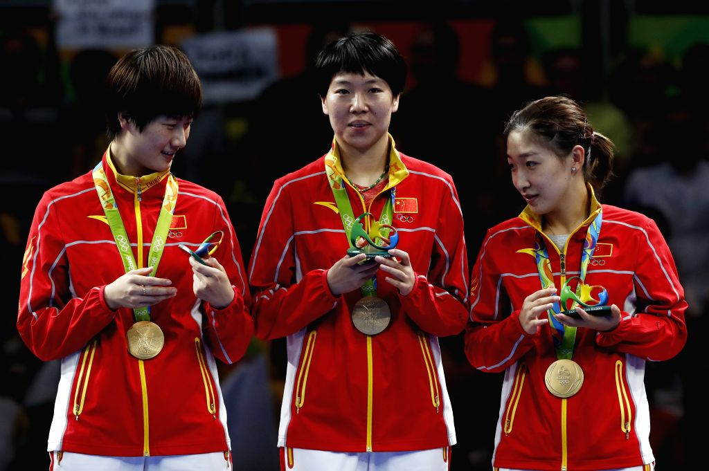 RIO DE JANEIRO, Aug. 16, 2016 - China's Ding Ning (L), Li Xiaoxia (C) and Liu Shiwen attend the awarding ceremony for the women's team final of table tennis at the 2016 Rio Olympic Games in Rio de ...
