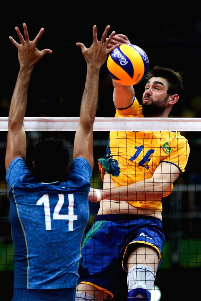 RIO DE JANEIRO, Aug. 17, 2016 - Brazil's Lucas Saatkamp (R) spikes the ball during the men's quarterfinal of Volleyball between Brazil and Argentina at the 2016 Rio Olympic Games in Rio de Janeiro, ...