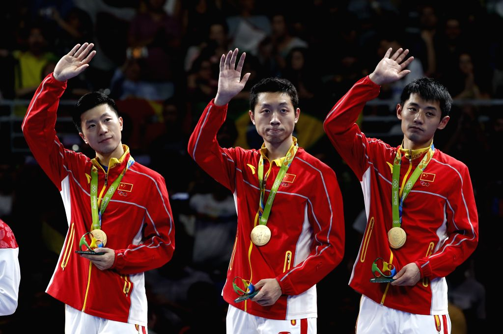 RIO DE JANEIRO, Aug. 17, 2016 - Gold medalists China's Ma Long, Xu Xin and Zhang Jike (L-R) greet the andience on the podium during the awarding ceremony for the men's team final of Table Tennis at ...