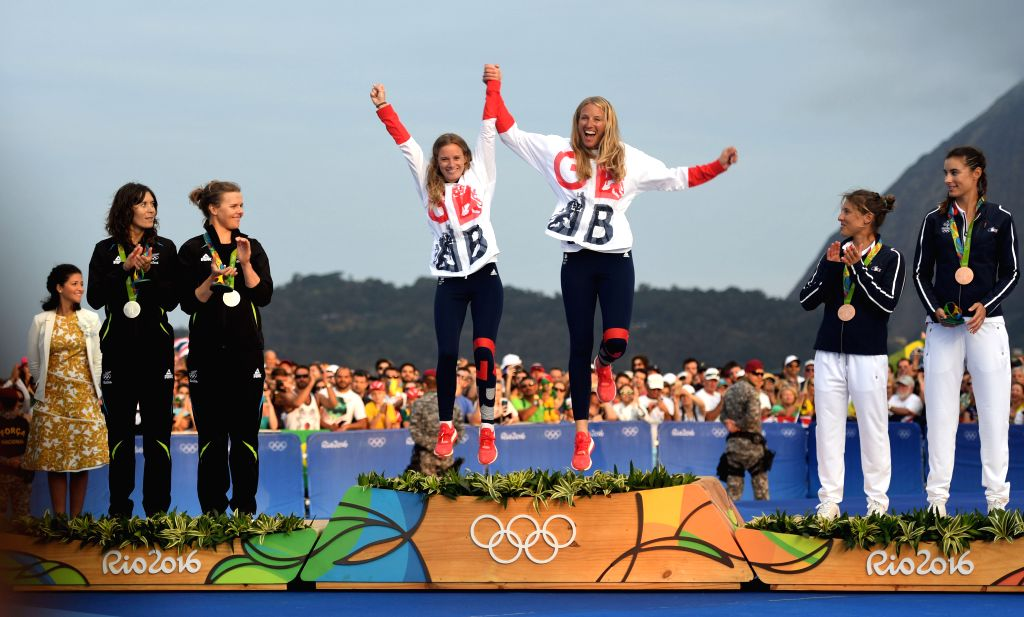 RIO DE JANEIRO, Aug. 18, 2016 - Gold medalists Britain's Hannah Mills and Saskia Clark jump onto the podium during the awarding ceremony for the 470 women medal race of Sailing at the 2016 Rio ...