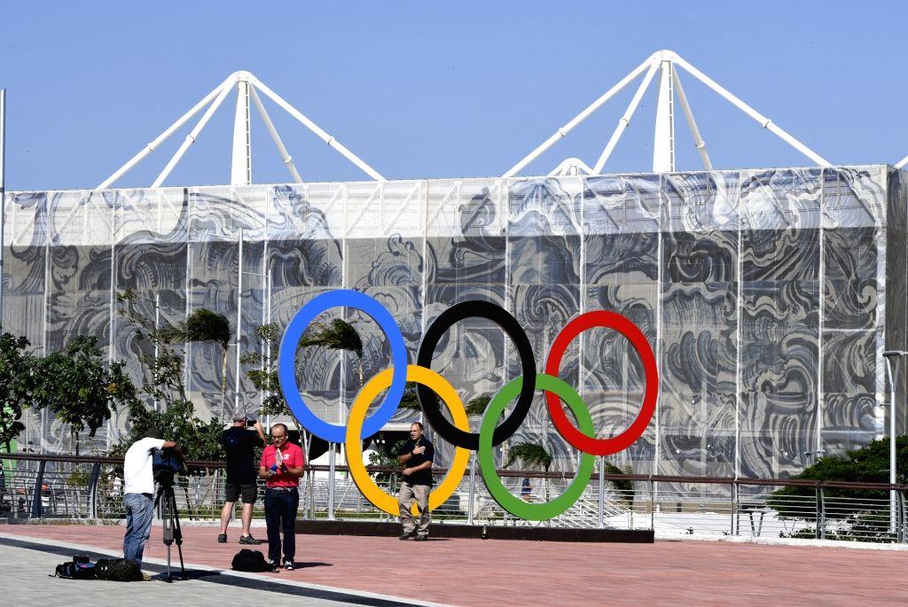 RIO DE JANEIRO, Aug. 4,2016 - Reporters work in front of the Olympic Aquatics Stadium in Rio de Janeiro, Brazil. (File Photo: Xinhua/Han Yan/IANS)