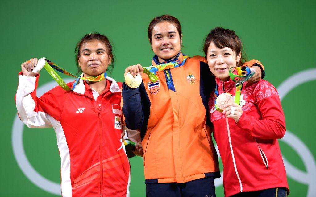 RIO DE JANEIRO, Aug. 6, 2016 - Gold medalist Sopita Tanasan (C) of Thailand, silver medalist Sri Wahyuni Agustiani of Indonesia (L) and bronze medalist Hiromi Miyake of Japan pose for photos during ...