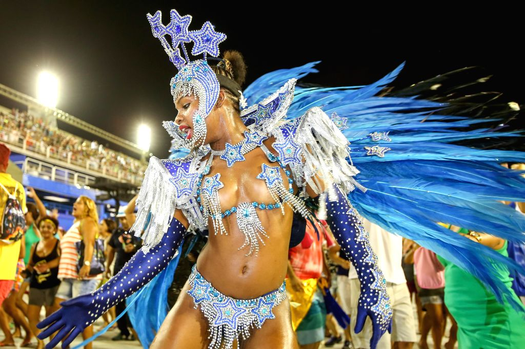 """A performer from the """"Em Cima da Hora"""" samba school participates in the first night of the annual Carnival parade at the Sambadrome in Rio de ..."""