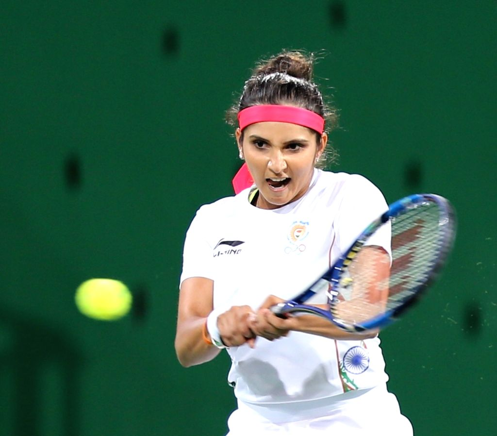 Rio de Janeiro: Indian tennis player Sania Mirza in action against Venus Williams and Rajeev Ram of US in the semi-finals of the mixed doubles tennis in Rio de Janeiro on Aug. 13, 2016. - Sania Mirza
