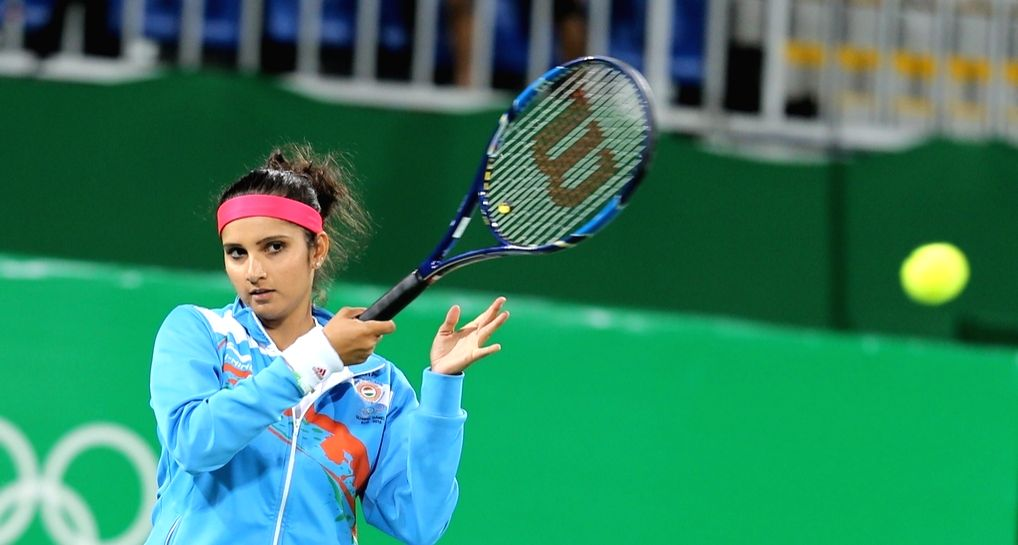 Rio de Janeiro: Indian tennis player Sania Mirza during warm up before the match against Andy Murray and Heather Watson of Britain  in mixed doubles tennis event  in Rio de Janeiro on Aug. 12, 2016. Sania and Bopanna entered the semi-finals of the mi - Sania Mirza