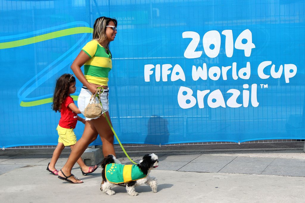 Brazilians walk by a logo of 2014 FIFA World Cup outside the Estadio do Maracana Stadium in Rio de Janeiro, Brazil, on June 15, 2014.