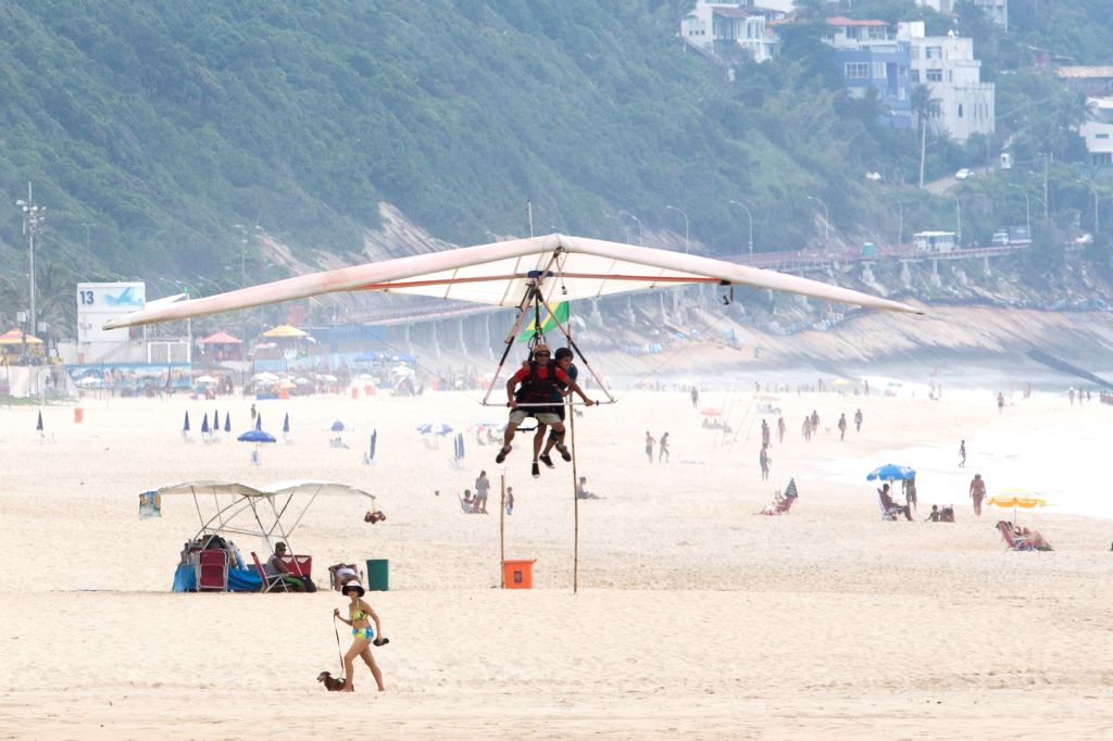 """People get ready to land with a hang glider, in Rio de Janeiro, Brazil, on March 14, 2015. There is a platform located in the """"Pedra Bonita"""" of ..."""