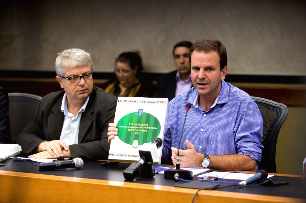 Mayor of Rio de Janeiro Eduardo Paes (R) presents the Handbook of Procedures for Big Events - 2014 World Cup during a launching ceremony in Rio de Janeiro, ...