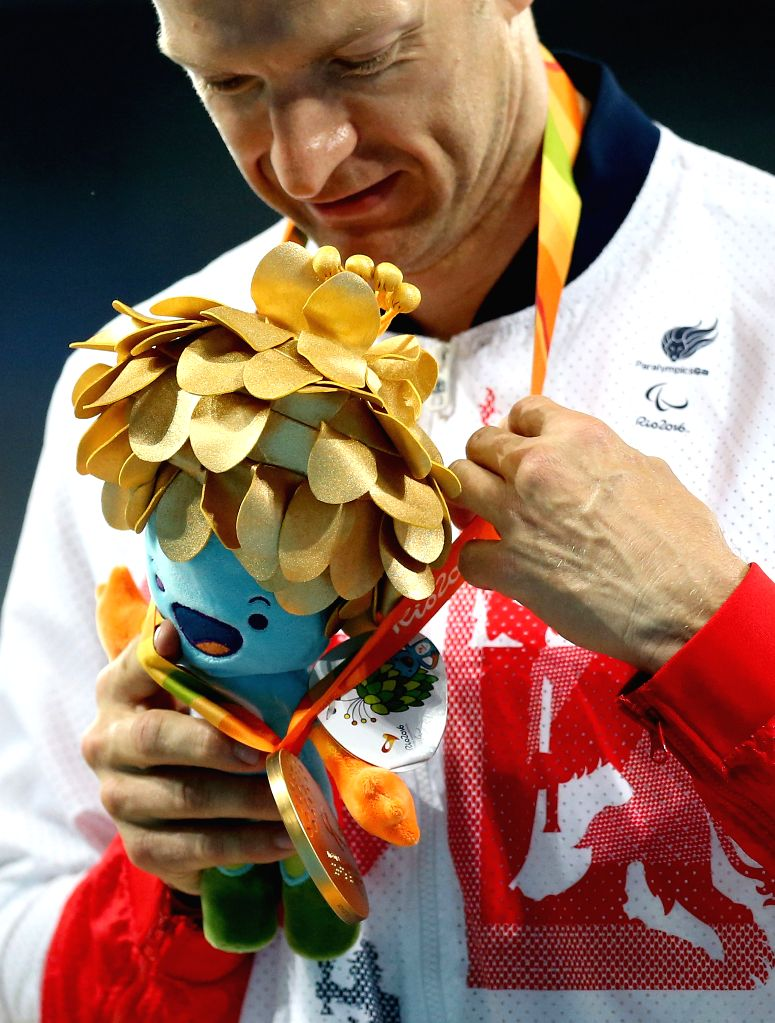 RIO DE JANEIRO, Sept. 11, 2016 - Richard Whitehead of Britain puts the gold medal on the mascot during the awarding ceremony of the men's 200m T42 final of athletics event at the 2016 Rio Paralympic ...