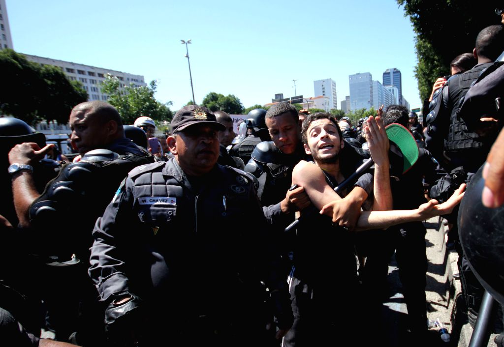 """Policemen arrest a person participating in the """"Cry of the Excluded"""", carried out in parallel with a parade to commemorate Brazil's Independence ..."""