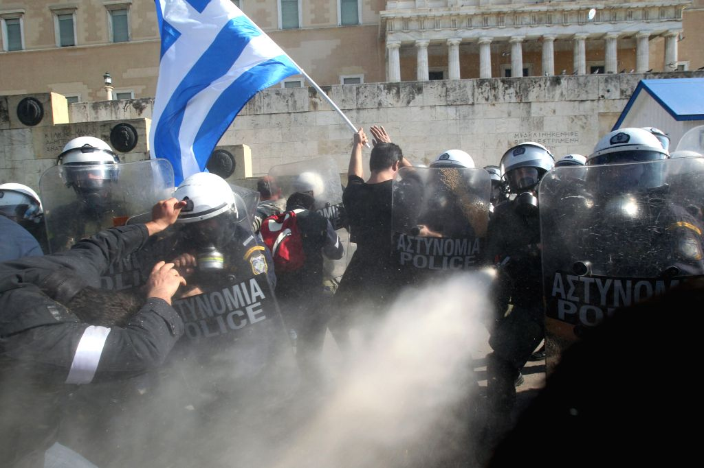 Riot policemen clash with farmers protesting against tax measures and changes in the social security system during a rally in front of the Parliament, in Athens, ...