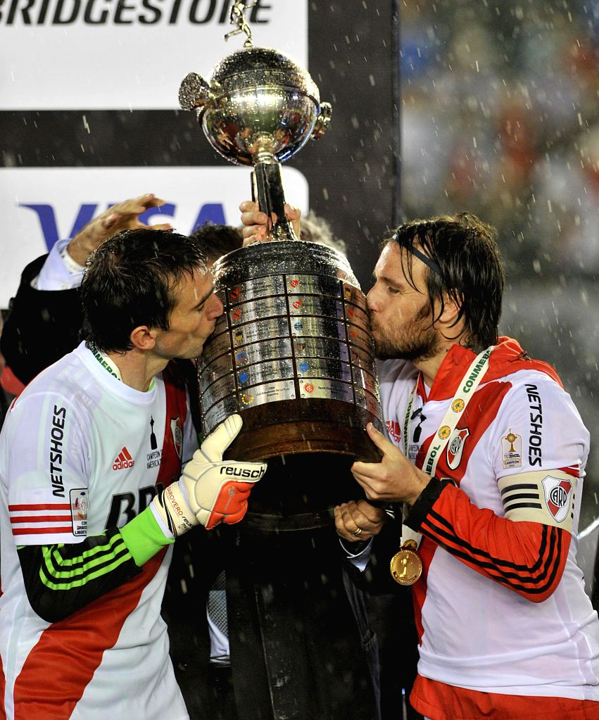 River Plate's players Marcelo Barovero (L) and Fernando Cavenaghi (R) celebrate with the trophy at the end of the second final match of Copa Liberators against ...