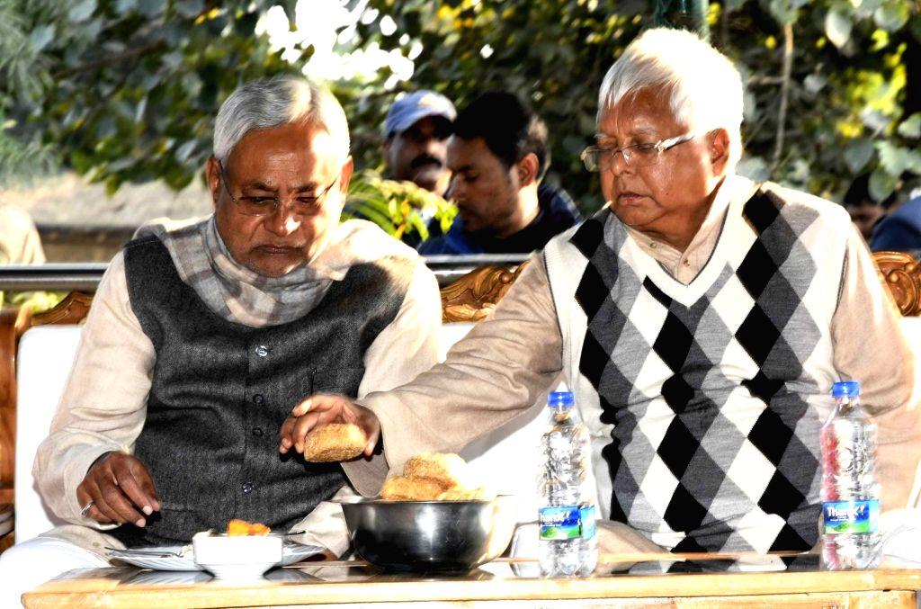 RJD chief Lalu Prasad Yadav servers puri to Bihar Chief Minister Nitish Kumar on Makar Snakranti in Patna on Jan 14, 2017. - Nitish Kumar and Lalu Prasad Yadav