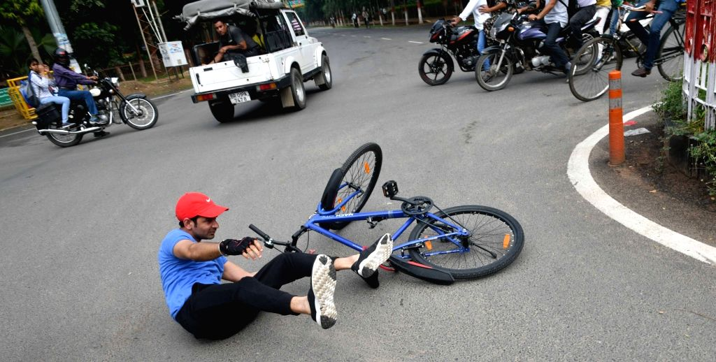 RJD leader Tej Pratap Yadav tumbles to the ground during the party's cycle rally, in Patna on July 26, 2018. - Tej Pratap Yadav