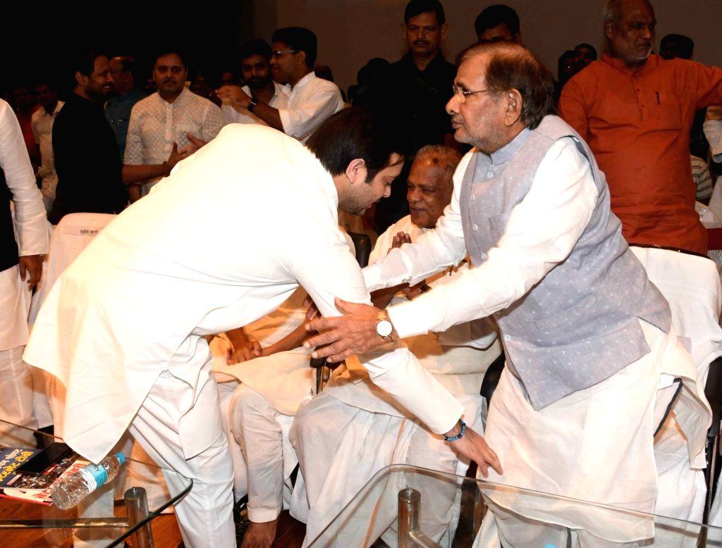 RJD leader Tejashvi Yadav touches the feet of Loktantrik Janata Dal leader Sharad Yadav during a programme organised on the death anniversary of Ram Manohar Lohia on his death anniversary, in ... - Tejashvi Yadav and Sharad Yadav