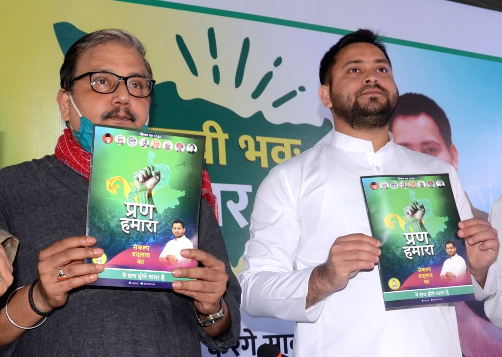 RJD leader Tejashwi Yadav accompanied by party leader Manoj Jha releases the party's election manifesto ahead of Bihar Assembly elections, in Patna on Oct 24, 2020. - Tejashwi Yadav